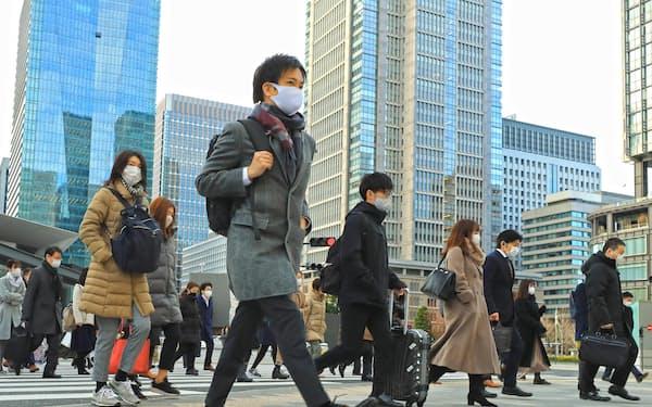 仕事始めを迎え、マスク姿で通勤する人たち(4日、東京。丸の内)