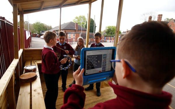 新たに設けられた屋外学習スペースで楽器を演奏するイングランドの小学生=ロイター