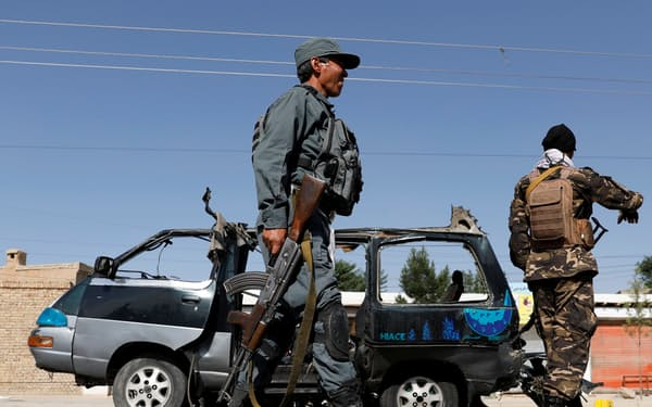 カブールで、爆発で破損した自動車を調べる警察官ら(3日)=ロイター