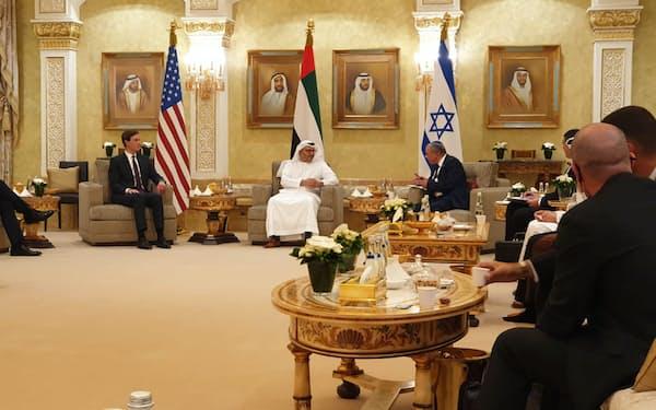 UAEがイスラエルとの国交を正常化したのも、中東で当面は緊張緩和を志向する動きが生まれたことを示している(20年8月、初めてアブダビを訪れ、UAE側と会談するイスラエルの訪問団)=ロイター
