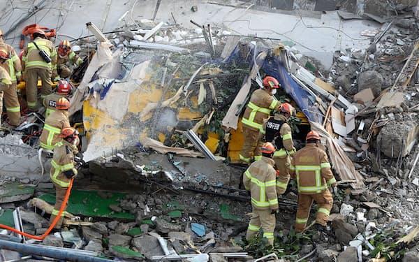 ビルの倒壊現場で救出作業にあたる消防隊員=ロイター