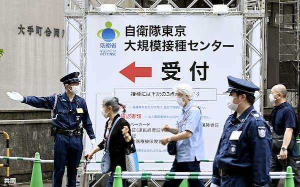 自衛隊が運営するワクチン大規模接種センター東京会場に向かう人たち(5月、東京都千代田区)=共同