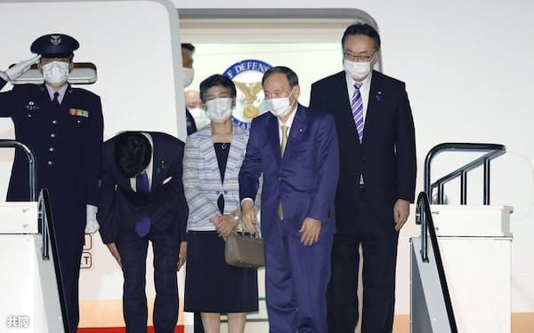 G7サミット出席のため、英国に向け出発する菅首相(右から2人目)。中央は真理子夫人=10日午後、羽田空港