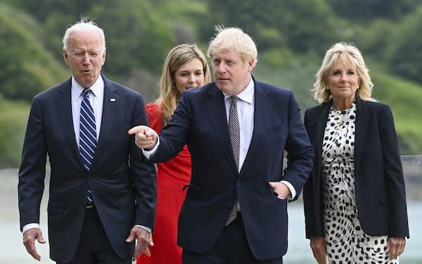 G7会議に先立ち、夫人らと海辺を歩くバイデン米大統領(左)とジョンソン英首相(右から2番目)=AP