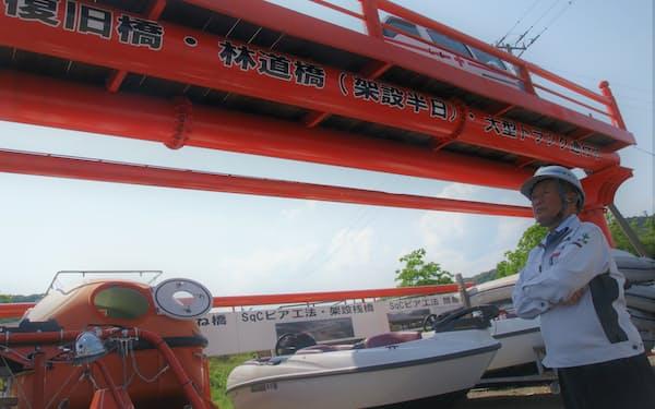 独自開発した災害復旧時の架設橋を見上げる高野広茂・高知丸高会長(高知県南国市)