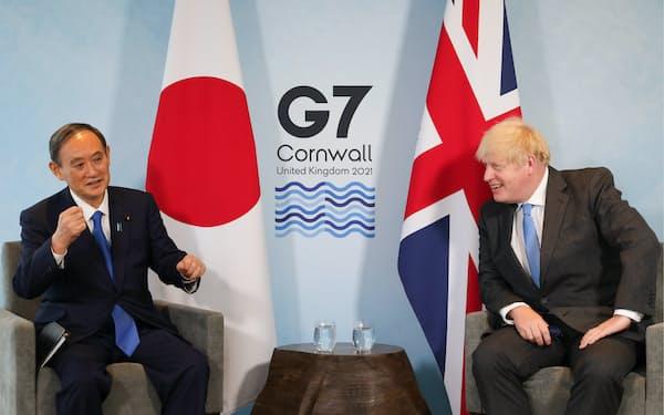 ジョンソン英首相(右)と首脳会談に臨む菅首相(11日、英コーンウォール)=英首相官邸提供