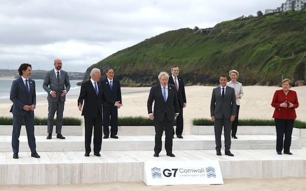 G7が開幕し、記念撮影に臨む各国首脳(11日、英コーンウォール)=AP