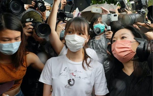 12日、香港の刑務所を出所した周庭氏(中央)=AP
