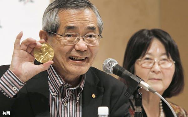 スウェーデンから帰国し、ノーベル化学賞のメダルを手に記者会見する根岸英一さん。右は妻すみれさん=2010年12月、千葉県成田市内のホテル