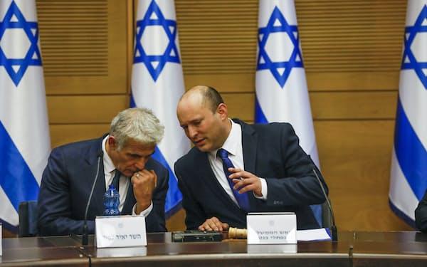 ベネット首相㊨は23年にラピド外相㊧に首相ポストを譲る輪番制で合意(13日、エルサレム)=AP
