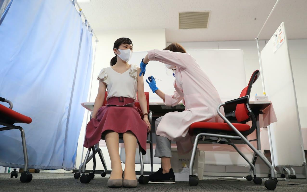 日本航空が職域接種を開始し、ワクチン接種を受ける客室乗務員㊧(14日、東京都大田区)