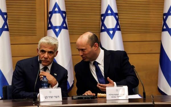 初閣議を開いたイスラエルのベネット首相㊨とラピド外相(6月13日、ロイター)