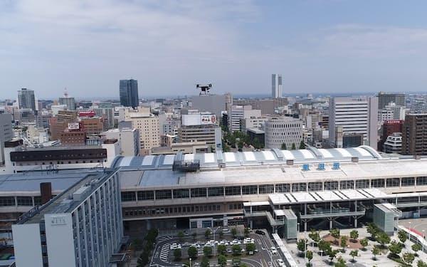 新潟駅南口上空を飛ぶドローン(中央、12日)