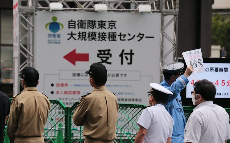 大規模接種センターでの自衛官や警察官らへの接種が始まり、「危機管理要員専用」の列に並ぶ人たち(14日、東京・大手町)