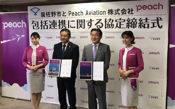 大阪府泉佐野市で15日、地域活性化へ包括提携を結んだ千代松大耕市長(左から2人目)とピーチアビエーションの森健明最高経営責任者(CEO=右から2人目)