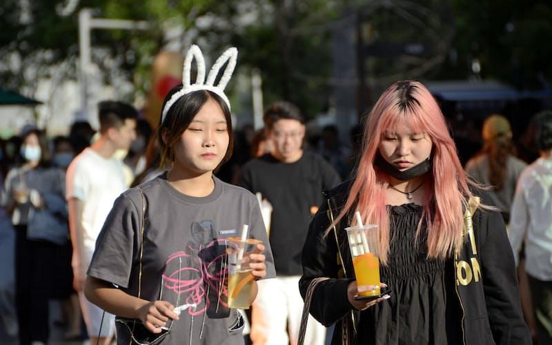 北京市内の繁華街を歩く若者たち=共同