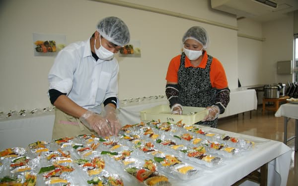 ボランティアで弁当を詰める井上詩音君㊧(高知県南国市の大篠子ども食堂)