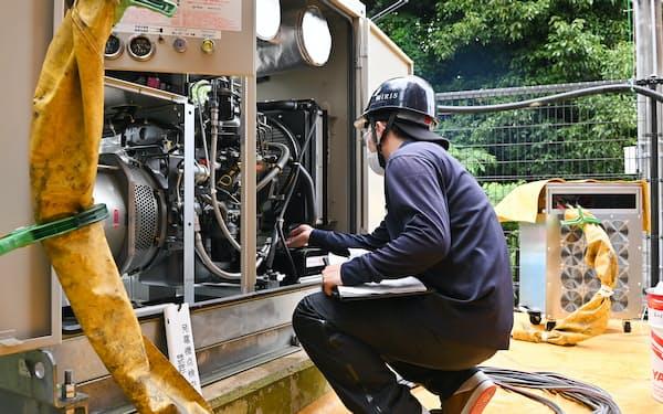 自家発電機に試験機(右奥)をつなぎ、規定の負荷をかけて検査する(16日、京都府宇治市)