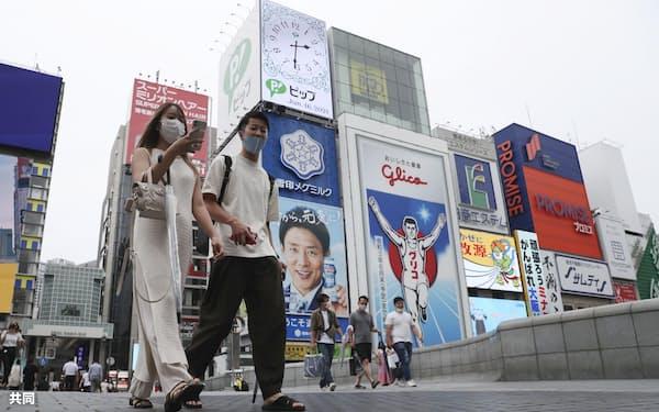 大阪・ミナミを歩くマスク姿の人たち(16日午後)=共同