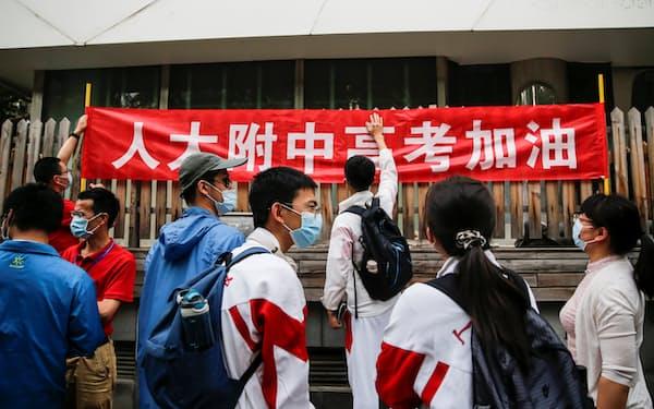 受験生を「加油(がんばれ)」と励ます横断幕を掲げる高校生(21年6月7日、北京市)=ロイター