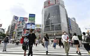 東京・渋谷のスクランブル交差点をマスク姿で歩く人たち(11日)=共同