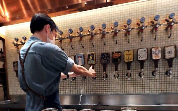 緊急事態宣言の解除を前に開店の準備をするビアレストランの店員(東京都新宿区のよなよなビアワークス 新宿東口店)