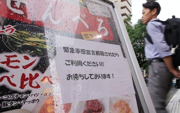 飲食店の看板には宣言解除後の利用を呼びかける紙があった(17日、名古屋市中区)