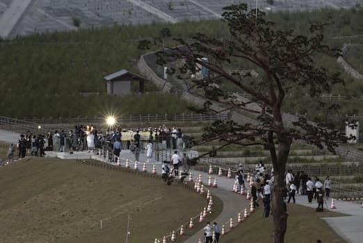 「奇跡の一本松」(右手前)からスタートした岩手県陸前高田市の聖火リレー(左奥)=17日(共同)