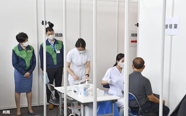 東京五輪・パラリンピックの関係者向けの接種会場を視察する小池東京都知事(左端、18日午後)=共同