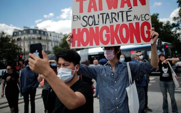 「台湾は香港と連帯する」と書かれたプラカード。かつては連帯感もあったが、環境は変わりつつある(20年7月、パリ)=ロイター