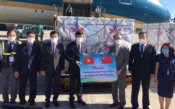 ベトナムに到着した中国製ワクチンを出迎えるグエン・タイン・ロン保健相(左から4人目)ら(20日、ハノイ市のノイバイ国際空港)=国営ベトナム通信