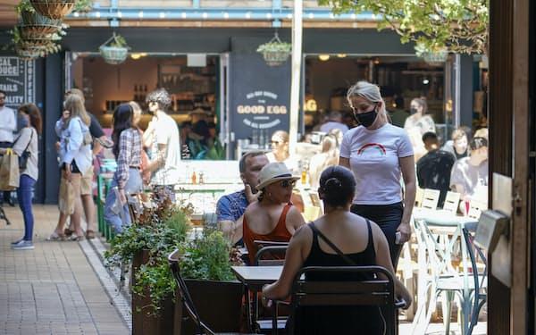 英国はロックダウンを徐々に緩和して飲食店などは営業できるようになったが、感染の再拡大を受けて全面的な解除は1カ月延期した(14日、ロンドン)=AP