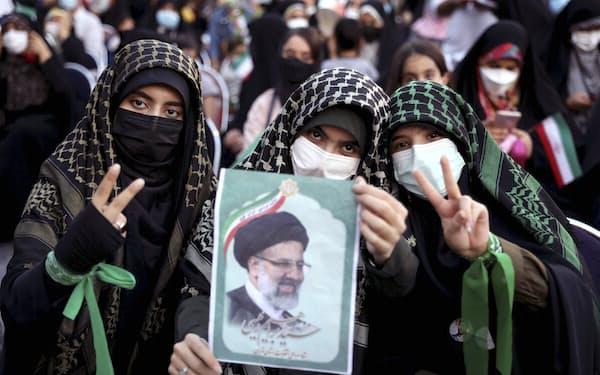 イラン大統領選でライシ師の当選を喜ぶ支持者ら(19日、テヘラン)=AP
