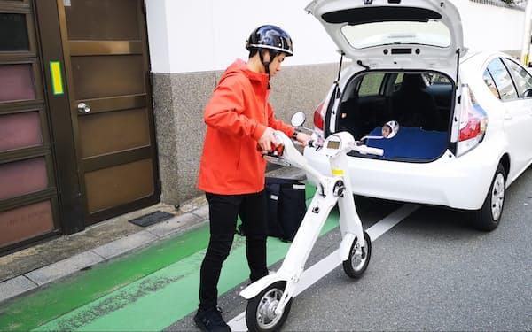 顧客にシェアカーを届け、EVバイクで戻るスタッフ