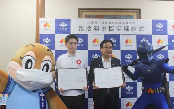 協定書に署名した南海電鉄の遠北社長(写真右)と大阪府の吉村知事(21日)