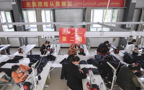 米政府は新疆ウイグル自治区からの綿製品輸入を禁じている(同地域の縫製工場のウイグル族作業員ら、5月)=共同