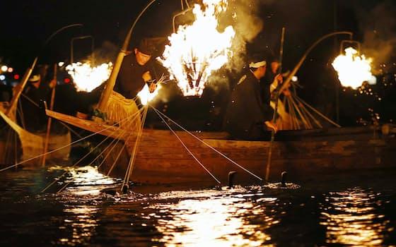 「長良川鵜飼」が開幕し、かがり火の下でアユを追う鵜匠とウ(21日夜、岐阜市)=共同