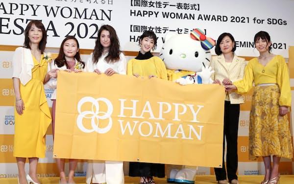 国際女性デーのイベントでSDGsに貢献したとして表彰された、一般社団法人「Colabo」代表の仁藤夢乃さん(左から2人目)、俳優の剛力彩芽さん(同4人目)、ハローキティら=8日午後、東京都内のホテル