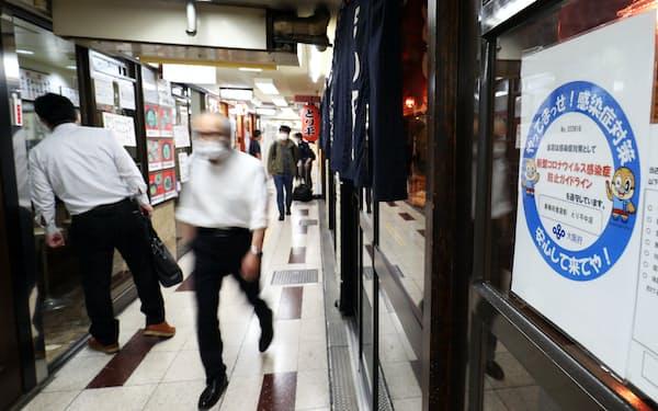 多くの店が営業を再開し、人が行き交う新梅田食道街(21日午後、大阪市北区)