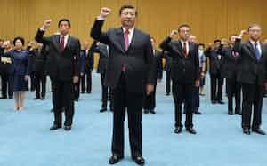 中国共産党の歴史を巡る展示を視察した後、拳をあげて宣誓する習近平国家主席(18日、北京)=新華社AP
