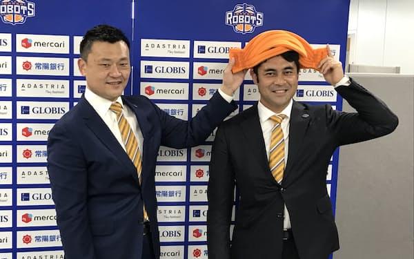 山谷社長㊧から社長用のオレンジの納豆ヘッドを「戴冠」された西村氏(22日、茨城県庁)