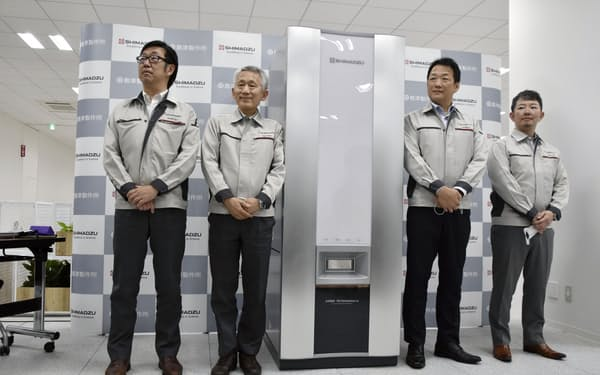 分析装置を紹介する島津製作所の田中エグゼクティブ・リサーチフェロー(左から2人目)ら(22日、京都市)=共同