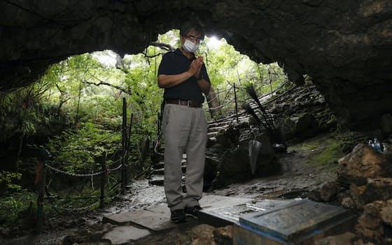 慰霊の日を迎え、沖縄戦最後の激戦地となった糸満市のガマで手を合わせる男性(23日午前)=共同