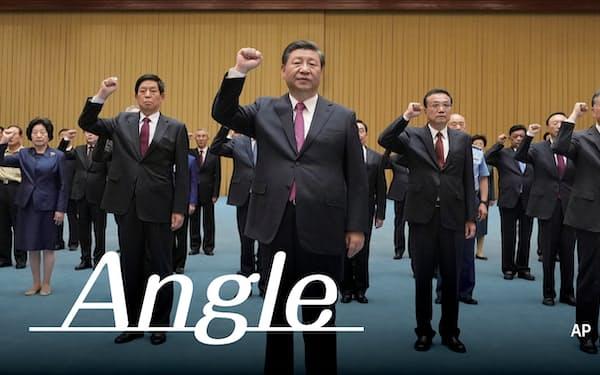右手の拳をあげて宣誓する習近平(シー・ジンピン)国家主席ら=AP