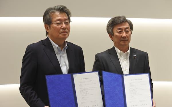 包括連携協定に署名した安川電機の小笠原社長㊨と九州大の石橋総長(23日、北九州市)