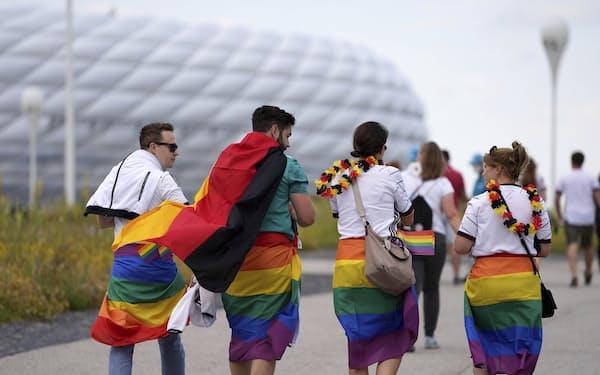 ハンガリーに抗議するため虹色の旗を身につけて、サッカーのドイツ対ハンガリーの試合会場に向かうサポーター(23日、ミュンヘン)=AP