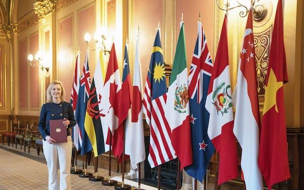 環太平洋連携協定(TPP)加盟国の国旗と英国のトラス国際貿易相=英政府提供・共同