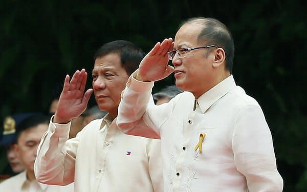 敬礼するフィリピンのドゥテルテ大統領(写真㊧)とアキノ前大統領=AP
