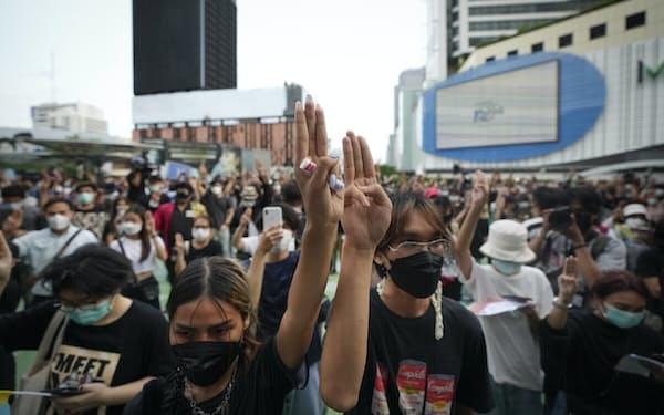 反体制運動を象徴する三本指を掲げるデモ隊(24日、バンコク)=AP
