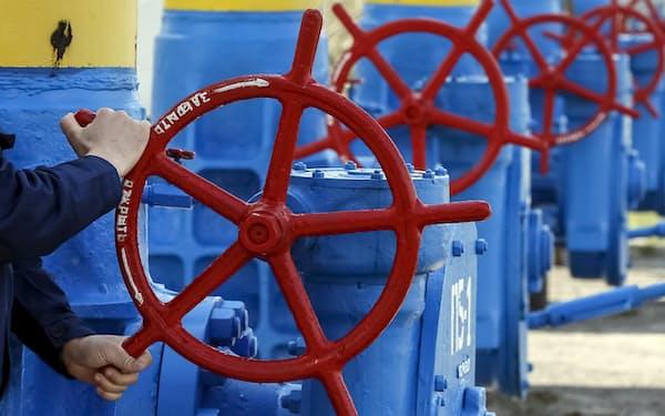 ガス圧縮機ステーションのバルブを回す従業員(2015年、ロシア・キエフ郊外)=ロイター